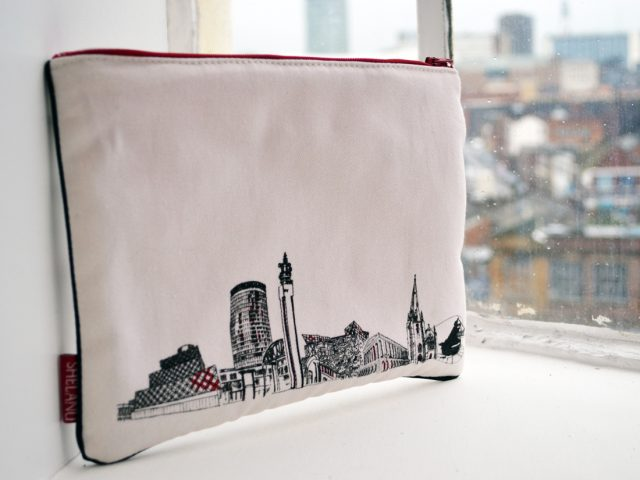 The i pad case sits on a windowsill. They are simple in design with a black and white line drawing of the skyline and red trimmings.