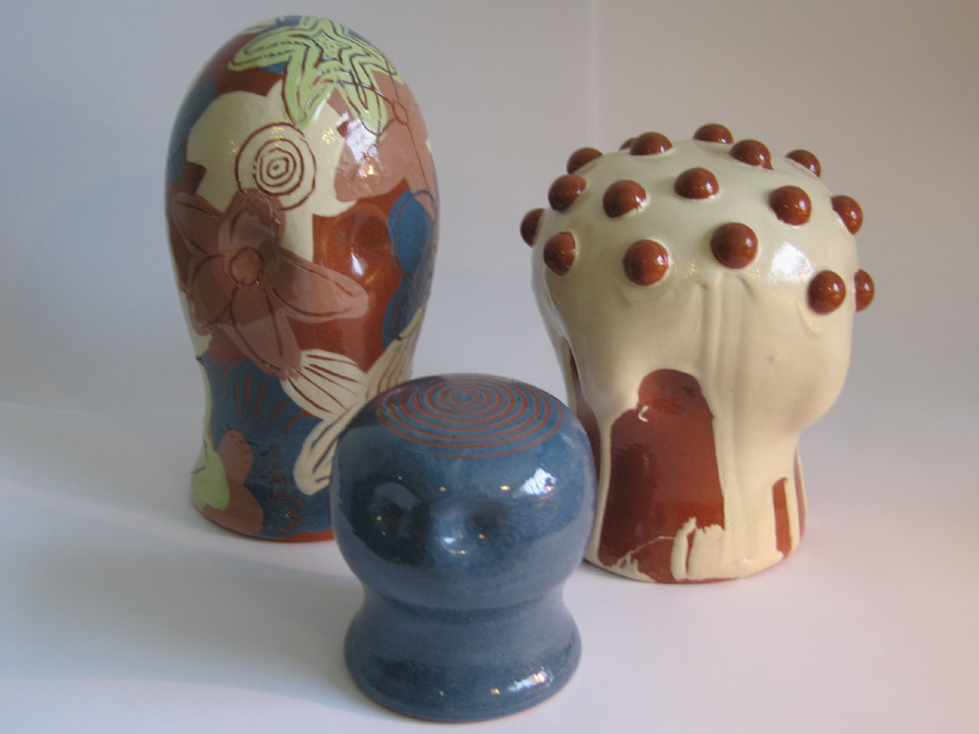 Three clay heads of various sizes with different coloured slips, shapes and decoration applied to them.