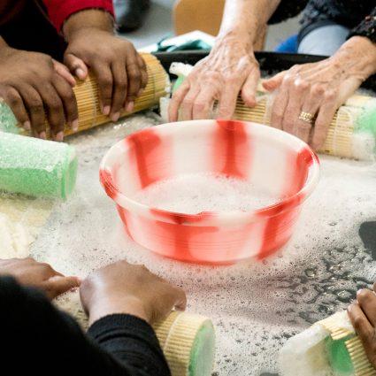 Older hands, soapy water, rolling fleece in bubble wrap.