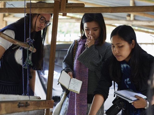 three women look at a loom, they have cameras and notebooks