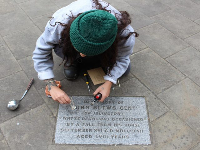 A young woman crouches over a memorial stone, she is pouring molten metal into the carved patterns.