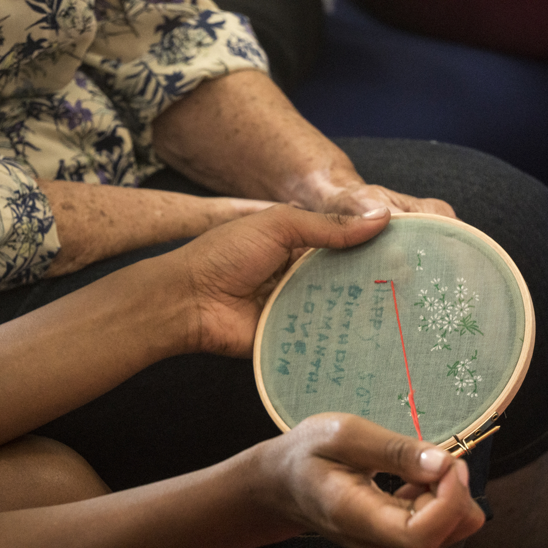 A close up of some hands embroidering simple text on material stretched over an embroidery hoop.