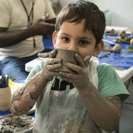 A boy pretends to use a wet clay bowl as a drinking cup.