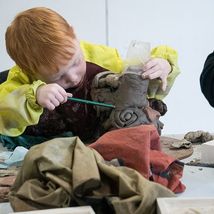 A young boy uses a plastic tool to make marks in a clay vessel.