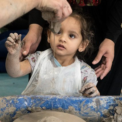 A young girl watches liquid clay drip onto the potters wheel.
