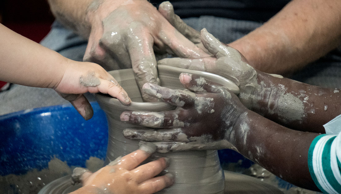 Hands work together on a potters wheel.