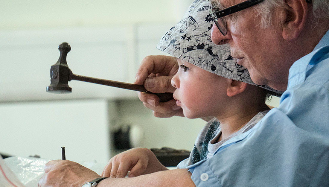 A older man teaches a child how to use a hammer and nail.