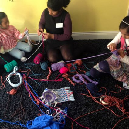 Girls sit on the floor with spools of wool scattered around them.