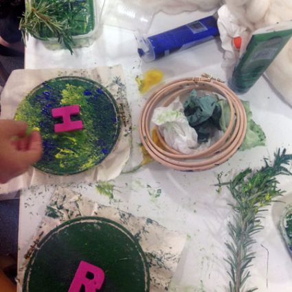 A table covered with embroidery hoops, paint and leaves.