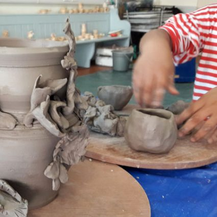 A very young child investigates a wet clay pot.
