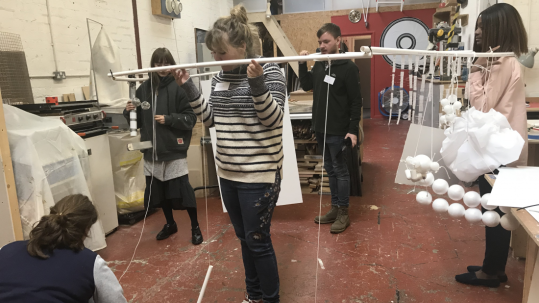 the group standing in workshop holding up a structure