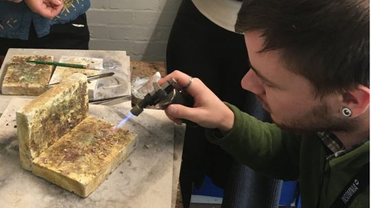 craft fellow using blow torch to solder silver
