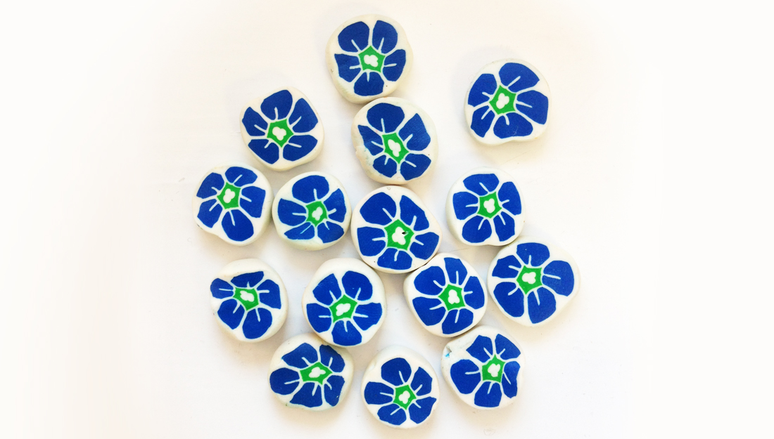 Handmade milliefiori white beads with blue and green flowers.