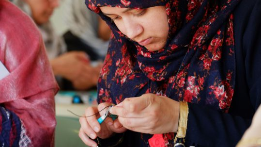 A participant concentrates on the fixings for her jewellery