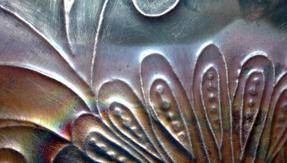 Close up of copper with flower design rolled into it.