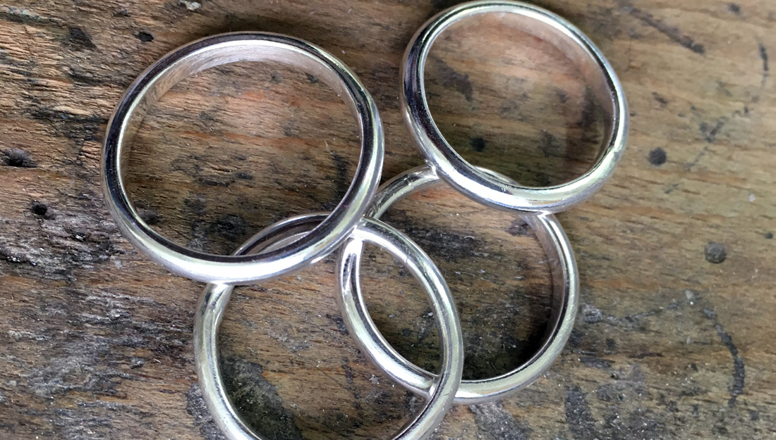 silver rings laying on a table.