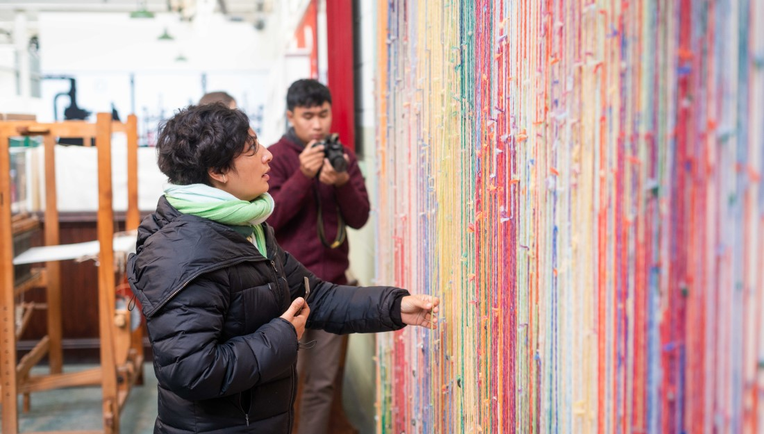 a delegate touches and admires colourful hanging threads installation on a wall