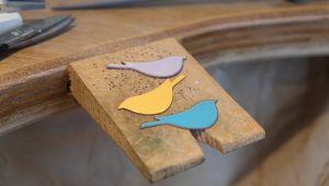 three enamelled birds on a jeweller's peg