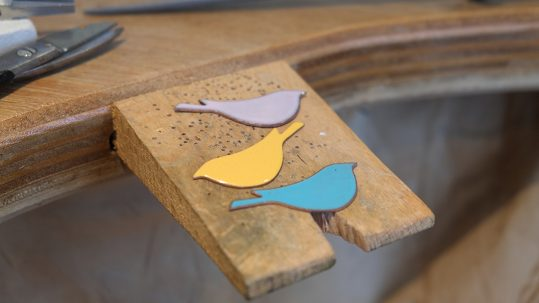 three enamelled birds on a jeweller's peg