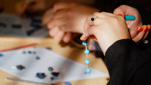 hands using pliers to fix fimo jewellery bracelet