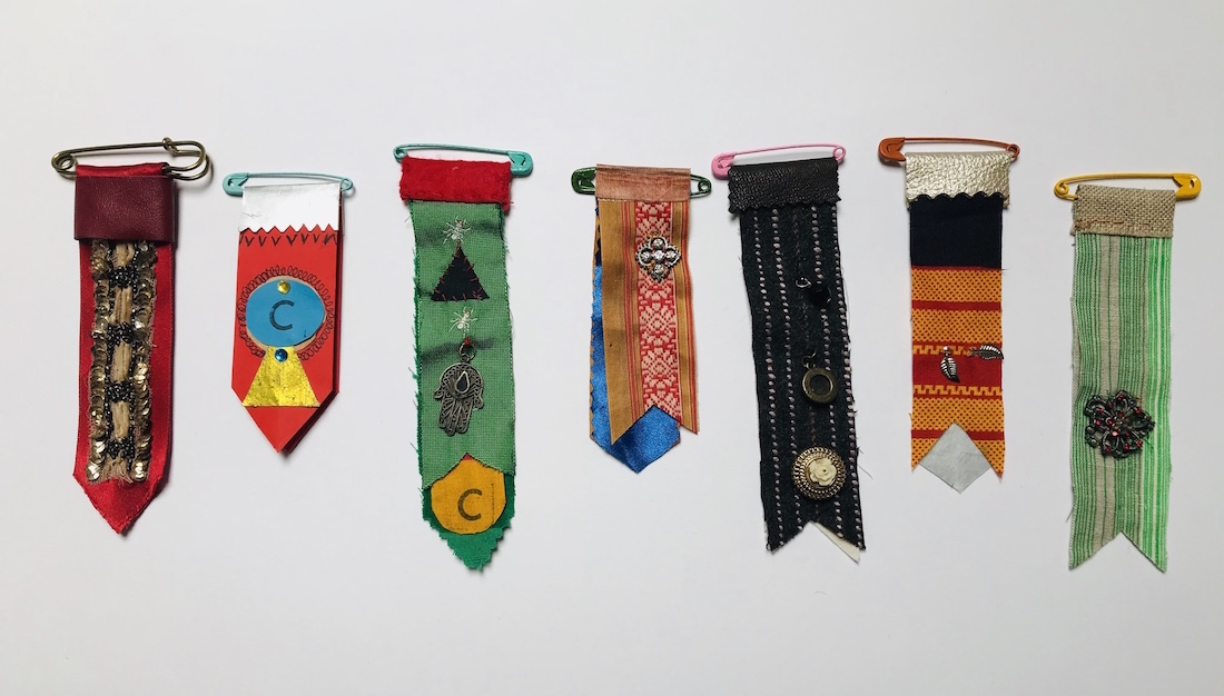 a row of 7 handmade fabric medals using various patterns and colours